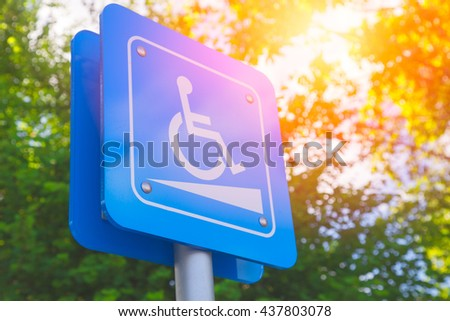 Disability slope or wheelchair ramp sign with green and sun light background. - stock photo