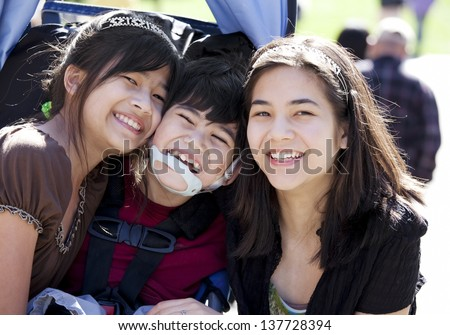 Disabled biracial boy in wheelchair surrounded by his bigger sisters, smiling. Child has cerebral  palsy. - stock photo