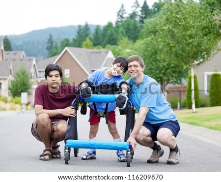 Disabled boy in walker surrounded by father and older brother while walking outdoors on street - stock photo