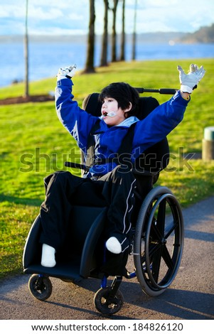 Disabled boy in wheelchair enjoying day at park, arms raised in happiness - stock photo