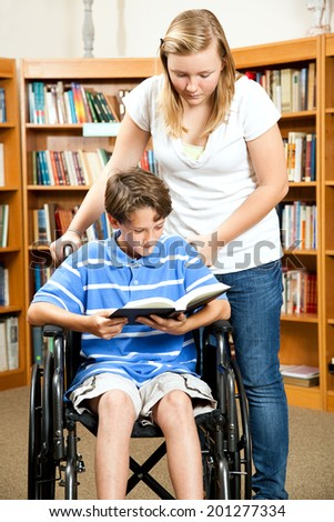 Disabled boy with a friend reading a book in the library.   - stock photo
