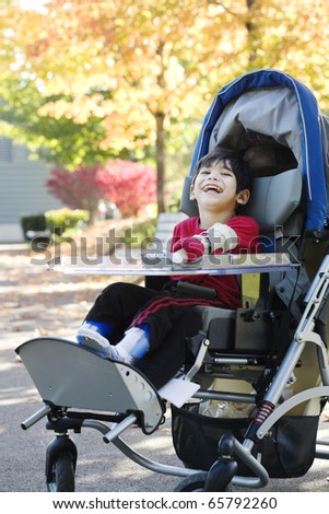 Disabled boy with cerebral palsy in medical stroller enjoying an autumn day outdoors at the park