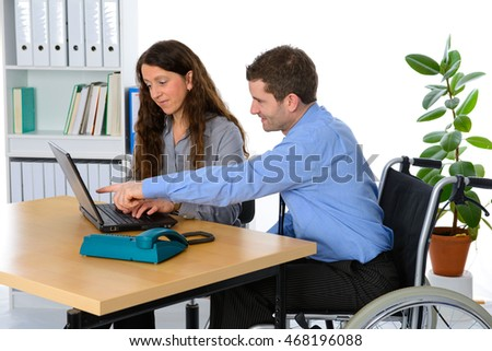 disabled businessman in wheelchair and his female colleague