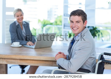 Disabled businessman working with partner in an office - stock photo