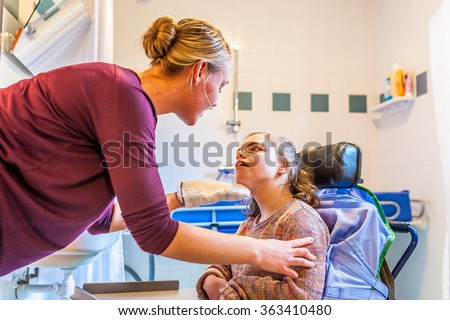 Disabled child in a wheelchair being cared for by a special needs nurse / Working with disability - stock photo