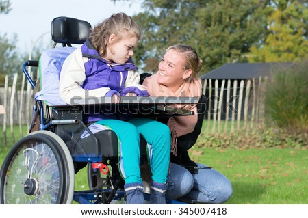 Disabled child in a wheelchair relaxing outside together with a care assistant / Working with disability - stock photo