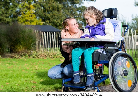 Disabled child in a wheelchair relaxing outside with a care assistant / Working with disability - stock photo