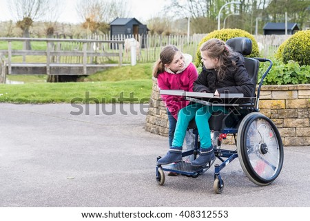 Disabled child in a wheelchair relaxing outside with a friend / Friends with disability