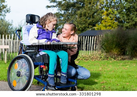 Disabled child in wheelchair relaxing outside with a care assistant/ Working with disability - stock photo