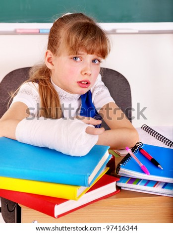 Disabled child with broken arm in classroom. - stock photo