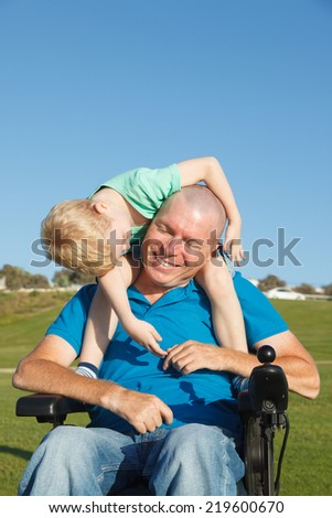 Disabled Father giving little son piggyback ride - stock photo