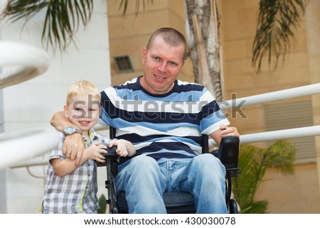 Disabled father play with his little son - stock photo