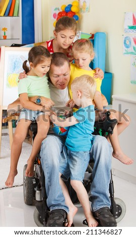 Disabled Father play with his little son and three daughters