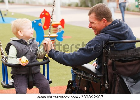 Disabled Father play with his little son on the playground.