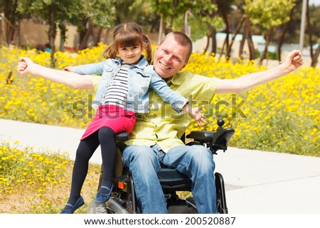 Disabled Father showing freedom with his little daughter.