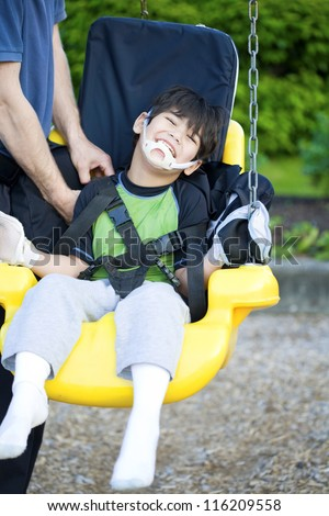 Disabled five year old boy getting strapped  into handicap swing - stock photo