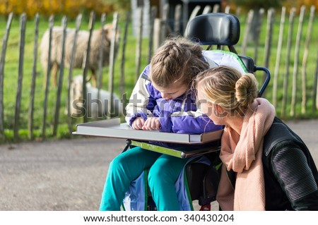 Disabled girl in a wheelchair relaxing outside with animals and the help from a care assistant / Working with disability - stock photo
