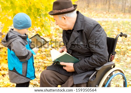 Disabled grandfather in a wheelchair and his cute young grandson enjoying leisure time together outdoors in an autumn park with the old man reading a book and the boy using a tablet computer - stock photo
