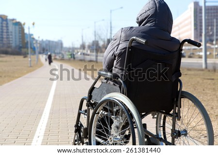 disabled handicapped person on wheeled chair during walk in city among people without disabilities - stock photo