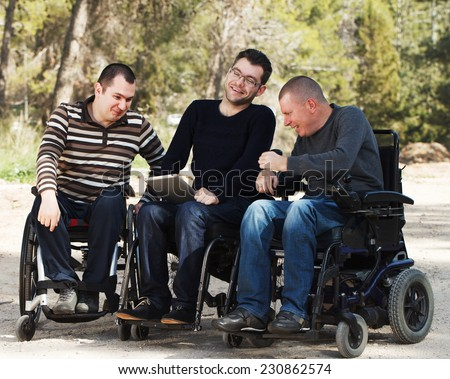 Disabled Happy friends with ipad outside - stock photo
