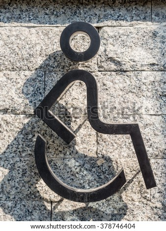disabled icon sign  wheelchair handicap symbol - on the stone wall - stock photo