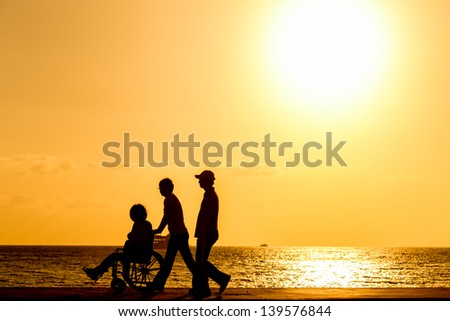 disabled in a wheel chair. Silhouettes - stock photo