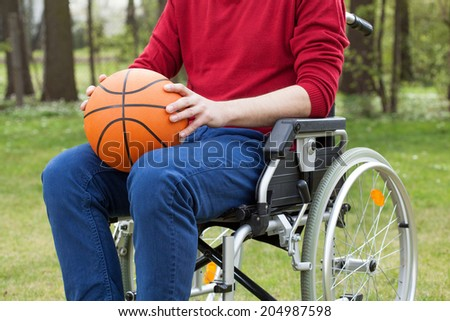 Disabled in a wheelchair holding a basketball ball - stock photo