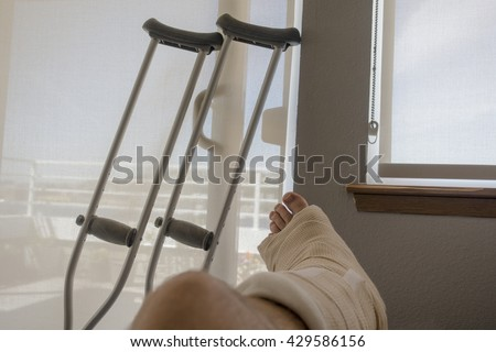 Disabled Injured Person With Sprained or Broken Ankle or Foot Sits Inside With Crutches Looking Outside the Sliding Glass Door Window on a Sunny Day.
