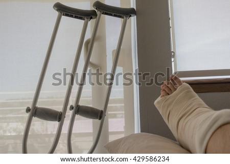 Người khuyết tật bị thương Với Ankle vỡ bong gân vàng chân vàng Với Nạng Ngồi Bên Nhìn bên ngoài cửa sổ trượt cửa kính là Sunny Day.