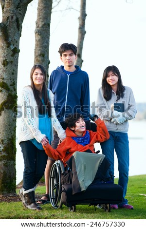 Disabled little boy in wheelchair surrounded by brother and sisters at lakeside. Child has cerebral palsy and children are all biracial - stock photo