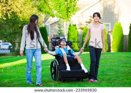 Disabled little boy in wheelchair walking with sisters on glassy lawn - stock photo
