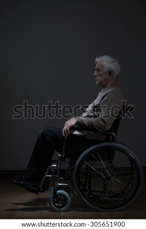 Disabled male pensioner is using in wheelchair - stock photo