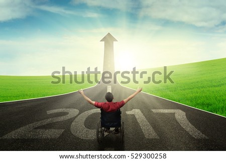 Disabled male sitting on a wheelchair and raising hands up while looking an upward arrow with numbers 2017 on the road