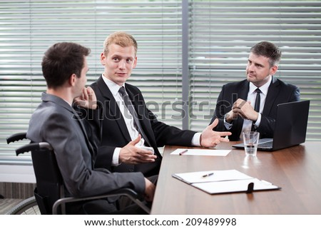 Disabled man and his co-workers during business meeting - stock photo