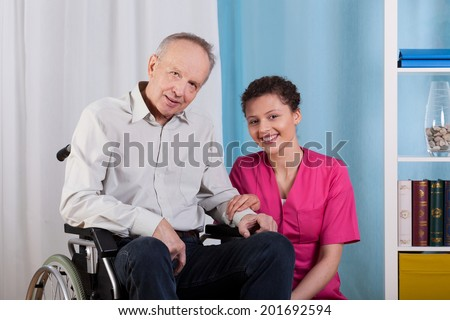 Disabled man and his nurse in a hospice - stock photo