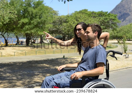 Disabled man in wheelchair and girlfriend in the park - stock photo