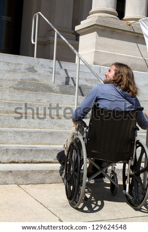 Disabled man in wheelchair looks for a ramp to gain access to a public building entrance. - stock photo