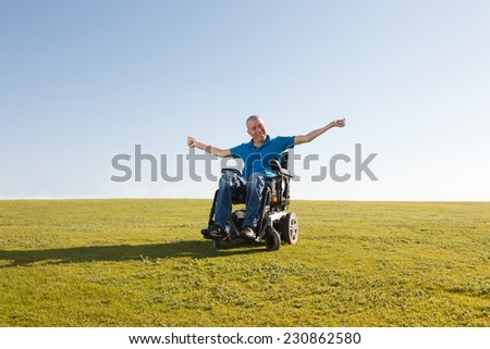 Disabled man in wheelchair shows freedom - stock photo