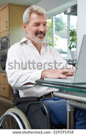Disabled Man In Wheelchair Using Laptop At Home - stock photo