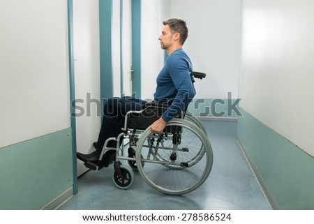 Disabled Man On Wheelchair Entering In Room - stock photo