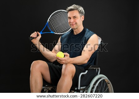 Disabled Man On Wheelchair Holding Racket And Ball - stock photo