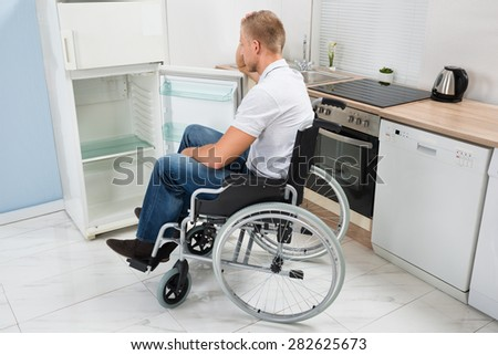 Disabled Man On Wheelchair Look Into An Empty Refrigerator