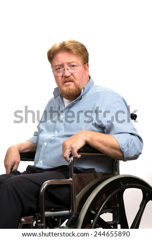 Disabled man sitting in a wheelchair poses with a serious expression on his face. - stock photo