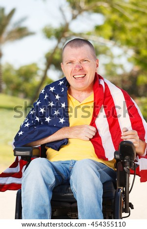 Disabled man sitting in wheelchair with flag of USA on the sholders - stock photo