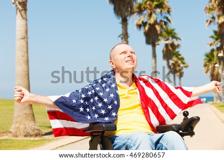 Disabled man sitting in wheelchair with flag of USA showing freedom