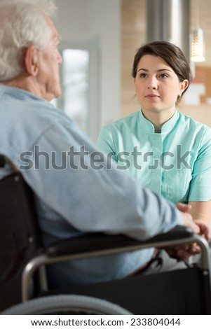 Disabled man using wheelchair talking with nurse - stock photo