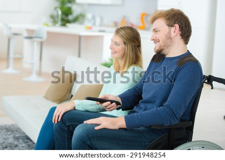 Disabled man watching TV with is girlfriend