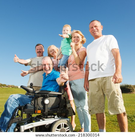 Disabled Man with family outside showing thumbs up. - stock photo