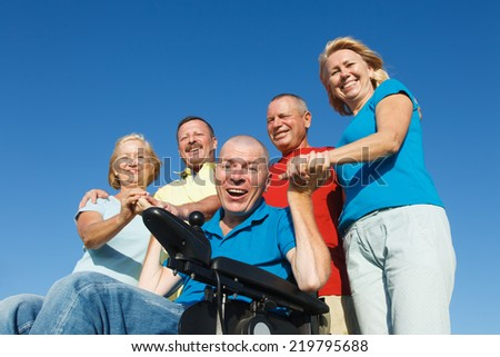 Disabled Man with family outside showing unity. - stock photo