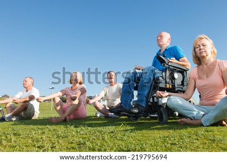 Disabled Man with Group of People practicing yoga outside. - stock photo